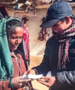 A VOM ministry worker gives this Nepali woman a Bible.